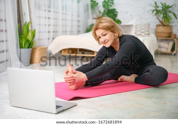 Fitnesstraining online, Seniorin zu Hause mit Laptop.