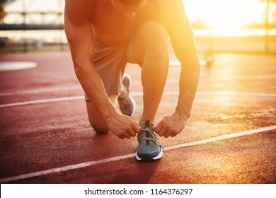 Fitness training outdoors. Handsome man working exercises in early morning with sunrise. Muscular man training outside. Sunny fitness morning.