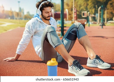 Fitness training. Young sportsman take a break after training. He siting on the ground and listening to music with headphones. Fitness, sport, lifestyle concept