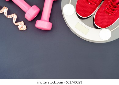 Fitness and weight loss concept, running shoes, dumbbells, tape measure, weighting scale, top view with copy space
