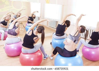 Fitness, Wellness and Helathy Lifestyle Concepts. Group of Five Caucasian Female Athletes Having Stretching Exercises with Fitballs Indoors.Horizontal Shot