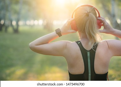 Fitness woman adjusting wireless headphones before starting jogging. Healthy lifestyle concept.
