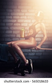 Fitness woman in athletic swimsuit drinking protein shake while workout in indoor gym