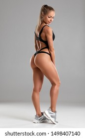 Fitness woman with beautiful butt on gray background. Sexy girl shaped glutes