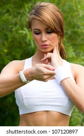 Fitness woman. Beautiful fit woman looking at wrist watch checking her pulse. Concept sport and fitness