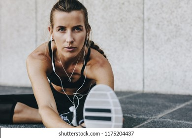Fitness woman bending forward stretching her leg sitting on the ground. Woman doing stretching exercises listening to music wearing earphones sitting outdoors.