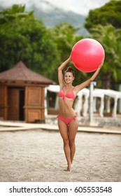 Fitness woman bikini model with fit ball at tropical beach outdoors. Fitness girl work out with pilates ball at beach. Female sport instructor hold yoga exercise ball outdoor in morning - yoga workout