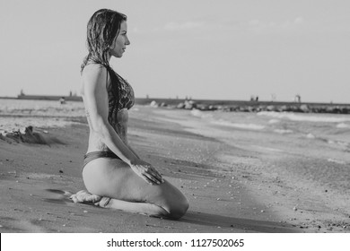 fitness woman with bikini sitting on the seashore