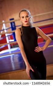 Fitness woman in catsuit posing in studio gym indoors