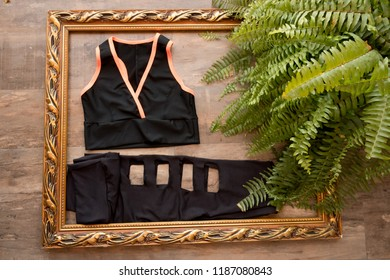 Fitness woman clothes, green palm leaves arranged on wooden background. Summer holidays vacation concept.