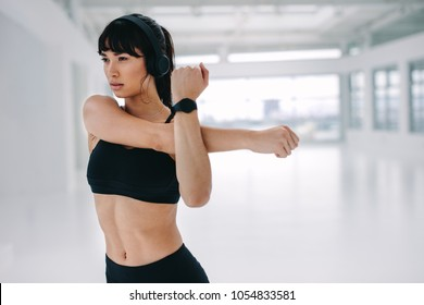 Fitness woman doing arm stretching exercise. Young woman stretching her arms at gym. Warmup workout at fitness studio.
