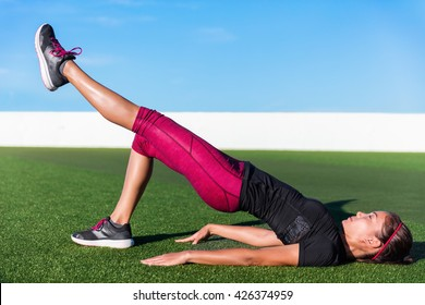 Fitness woman doing bodyweight glute single leg floor bridge lift exercices. Fit Asian woman exercising glutes muscles with one-legged floor bridge butt raise during summer in outdoor gym on grass.