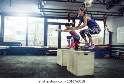 Fitness woman doing box jump workout at gym. Female athletes doing box jump workout at gym.