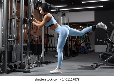 Fitness woman doing exercise for glutes, cable kickbacks. Athletic girl workout at the gym. Beautiful butt in leggings