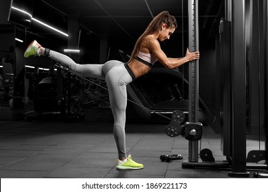 Fitness woman doing exercise for glutes, cable kickbacks. Athletic girl workout in gym