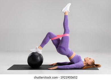Fitness woman doing glute bridge exercise with resistance band on gray background. Athletic girl working out - Shutterstock ID 1921903652