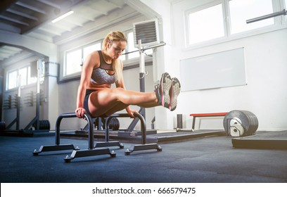 Fitness woman doing L Sit position on parallel bars, calisthenic workout