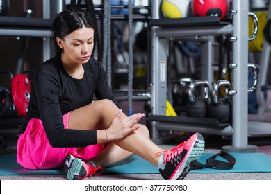 Fitness woman woman doing leg self massage at gym. Young female at gym taking a break from workout