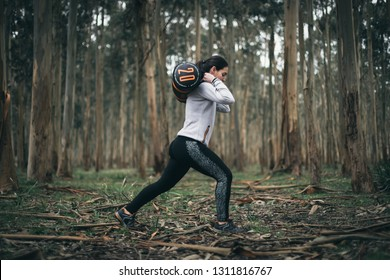 Fitness woman doing lunges outdoors with heavy bag during hiit and strength workout.