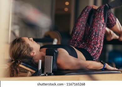 Fitness woman doing pilates workout lying on a fitness machine. Pilates woman at a gym doing exercises.