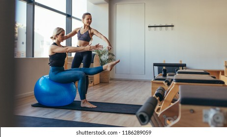 Fitness woman doing pilates workout sitting on an exercise ball at gym. Fitness trainer guiding a woman in pilates training.