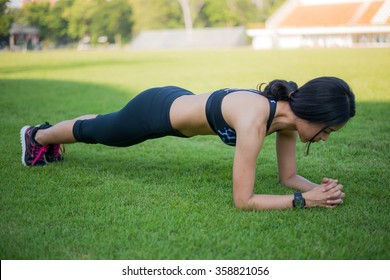 fitness woman doing plank core exercise workout on grass