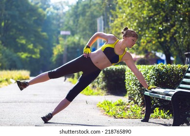 Fitness woman doing push-ups during outdoor cross training workout. Beautiful young and fit fitness sport model training outside.
