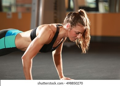 Fitness woman doing push-ups in a gym