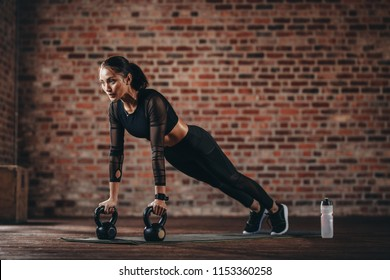 Fitness woman doing pushups with kettle bell at gym. Female athlete doing cross training at gym.