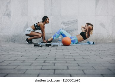 Fitness woman doing sit ups on exercise mat outdoors while her friend holds her legs. Women in fitness wear training outdoors.