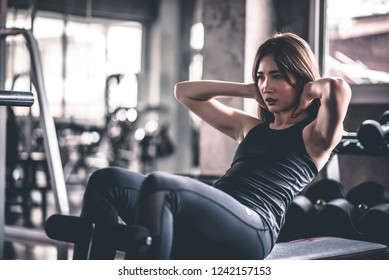 Fitness woman doing sit ups exercising at gym.