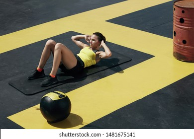 Fitness woman doing sit-ups exercise workout at gym. Sport girl exercising on yoga mat, doing abs crunches exercises outdoors at street