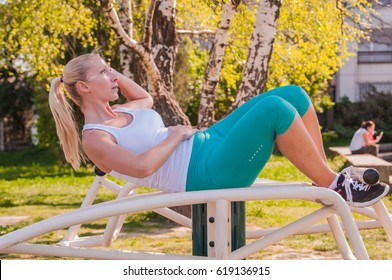 fitness woman doing situps in outdoor gym woking out strength training. Active woman exercising. Fit and sporty woman training outside