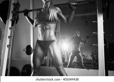 Fitness woman doing squats with the barbell at the gym. Smith Machine in the gym.  Fitness woman in the gym. Perfect fitness female figure. Fitness - concept of healthy lifestyle. Crossfit woman