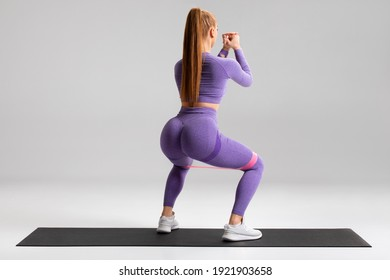 Fitness woman doing squats exercise for glute with resistance band on gray background. Athletic girl working out - Shutterstock ID 1921903658
