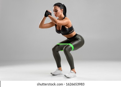 Fitness woman doing squats with resistance band on the gray background. Sporty girl squatting