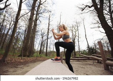 Fitness woman doing stepping up exercise in forest. Caucasian female model working out in nature.