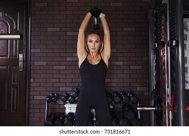 Fitness woman doing triceps exercise with dumbbells in the gym
