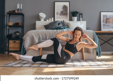Fitness woman doing twists exercise. Morning workout at home