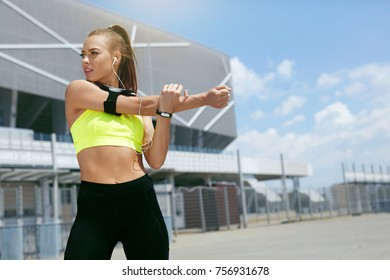Fitness. Woman Doing Workout Exercise On Street. Beautiful Girl With Fit Body In Stylish Sportswear With Sports Devices Listening Music While Stretching Arms Outdoors. High Resolution