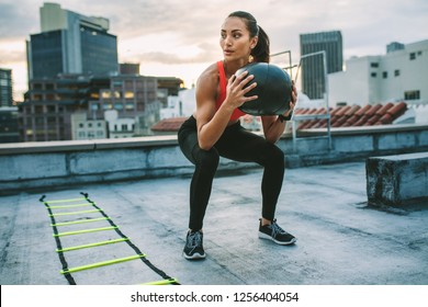 Fitness woman doing workout on rooftop using a medicine ball. Woman doing squats holding a medicine ball with an agility ladder by her side on rooftop.