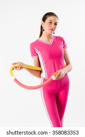 fitness woman dressed in pink sportswear working with hula hoop smiling
