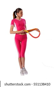 Fitness woman dressed in pink sportswear working with hula hoop. Isolated over white