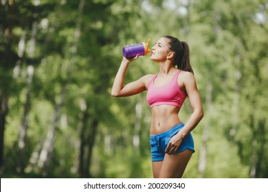 Fitness woman drinking water after running at park Thirsty sport runner resting taking a break with water bottle drink outside after training. Beautiful fit sporty caucasian girl.