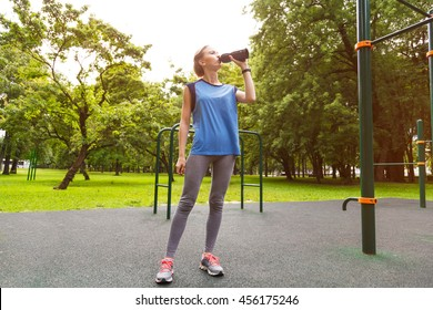 Fitness woman drinking water from bottle. Muscular young female at gym taking a break workout.