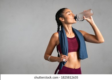 Fitness woman drinking water standing on gray background with copy space. Portrait of sweaty latin woman take a break after intense workout. Mid adult lady drink from water bottle after gym workout.