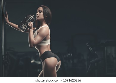 Fitness woman drinking water at workout in the gym. Pretty caucasian girl exercising cross fitness and bodybuilding sport concept. Abs muscle butt  and booty exercises in gym naked torso
