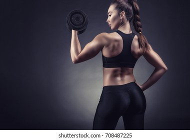 Fitness woman with dumbbells against a dark background. Back view. Sport concept