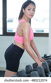 Fitness woman with dumbbells. Close-up shot of torso