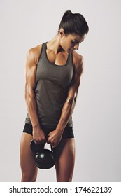 Fitness woman exercising crossfit holding kettle bell strength training biceps. Beautiful sweaty fitness instructor on grey background. Middle eastern female model with muscular fit and slim body.
